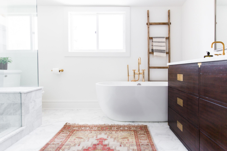 White bathroom with brass accents. Vintage runner on the ground