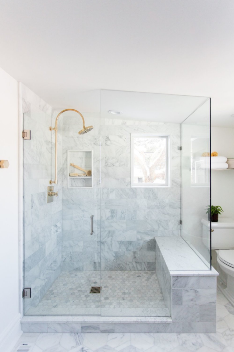White marble shower with glass door and brass hardware