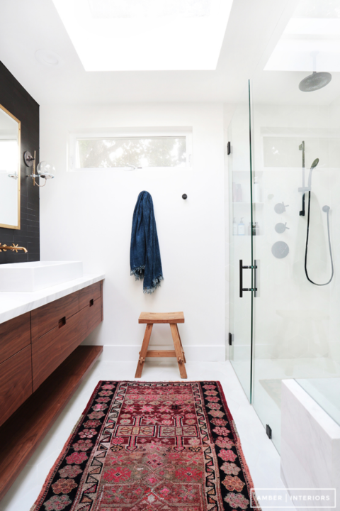 White bathroom with glass shower door, matte black hardware and wood cabinetry. Colorful area rug in front of the vanity