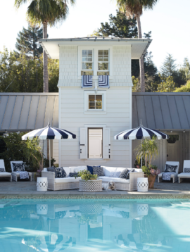 Exterior shot of white house with pool and blue and patio furniture with blue and white striped umbrellas