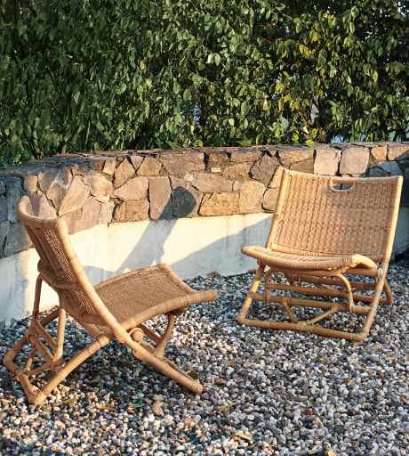 two wicker chairs on a pebble patio